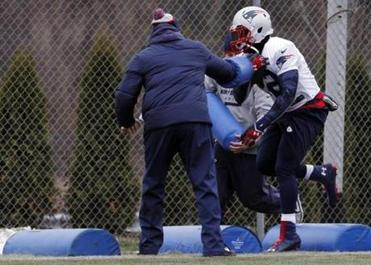 Patriots' Stevan Ridley secures the football as a staff member tries to jar it loose during a practice drill Thursday. Ridley has several costly fumbles this season.